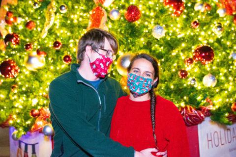Couple enjoying Zoo Lights in front of Christmas tree