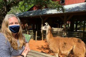 amy posing in front of llama exhibit