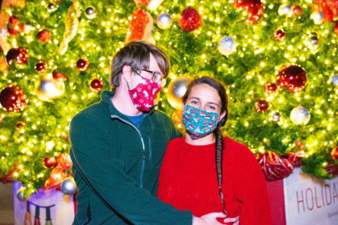 Couple enjoying Zoo Lights in front of Christmas tree
